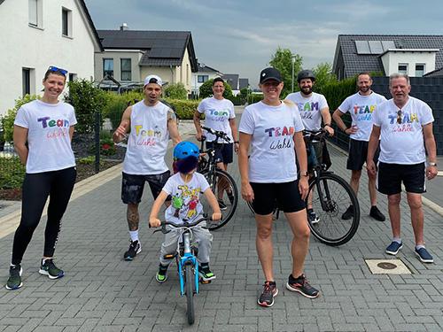 Muko-Spendenlauf 2021 - Gruppenbild Team Wahle: 7 Erwachsene und ein Kind auf dem Fahrrad, alle tragen selbstgemalte T-Schirts mit dem Teamnamen