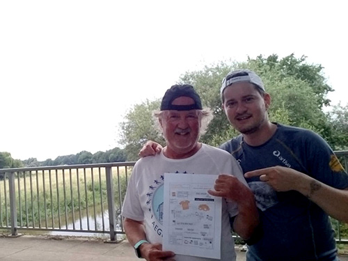 Muko-Spendenlauf 2021 - Wilfried und Dominik stehtn auf einer Brücke und zeigen dabei die Sketchnote zum Muko-Spendenlauf